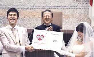 上地市長の前で誓約書を掲げる岩崎健一郎さん(左)と綾乃さん