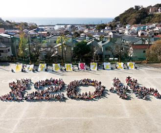 ▶約300人の児童が人文字で「120周年」を描いた=今月1日、大楠小のグラウンドで