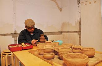 市営住宅を改修したアトリエ。手前の土器はワークショップに参加した地元住民の作品