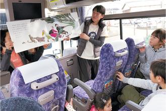 バスに乗り込み、読み聞かせを楽しむ子どもたち
