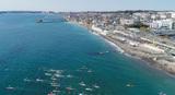野比海岸をパドルで漕ぎ進むSUPマラソンの出場選手と北下浦の海岸ロードを走るランナー(ゴール地点の若山牧水の碑付近)。ドローンを使って上空から。撮影写真提供=Yokosuka Paddle Club / M Nakagawa