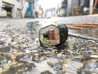 路上に転がる鉄火巻。捨てられたのか、落とし物か…