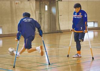 杖を軸に片足を振り子のようにしてボールを蹴る