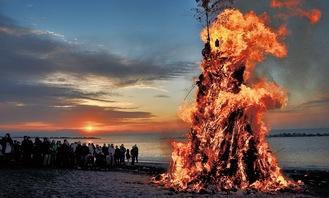 豪快に燃える「おんべ」。背後には房総半島に昇る朝日