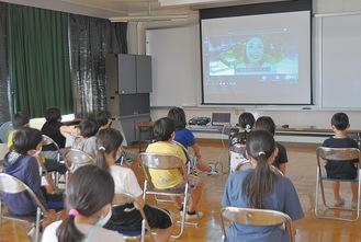 案内役の女性とスクリーン越しに会話する児童