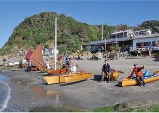 ビーチハウスの前に勢ぞろいした様々なタイプの木造自作艇とオーナーら