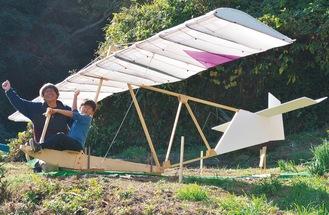 横6m×縦4mのグライダーに乗って拳を高く突き上げる高橋くんと制作者の吉江さん