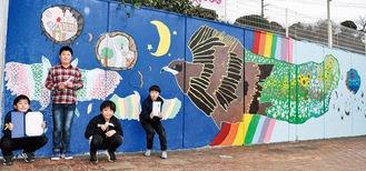 完成した壁画の前で感謝状などを見せる児童たち