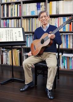 年季の入った楽譜と称号記を背景にギターを構える原さん