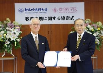 互いに調印した協定書を手にする鹿島理事長(左)と保々理事長