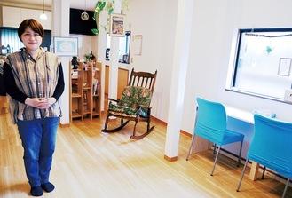 寄付された多くの家具が並ぶ室内に立つ菊池さん