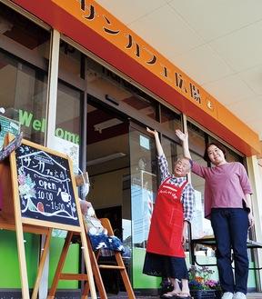オレンジ色の看板が目印(左が三澤さん、右が小松さん)