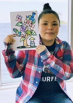 チラシを活用した貼り絵を手にする椎名さん