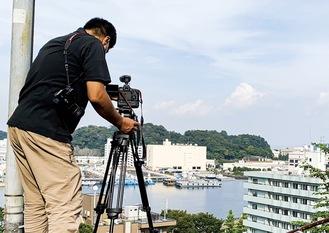 自前のカメラを担ぎながら市内各所を撮影する「いまただふみ」さん