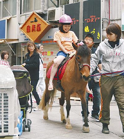 乗馬で商店街散歩