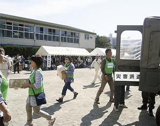 自衛隊の車両から物資を運び出す訓練参加者