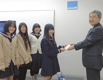 日本ユニセフ協会の三上氏に寄付金を渡す生徒(学校提供)