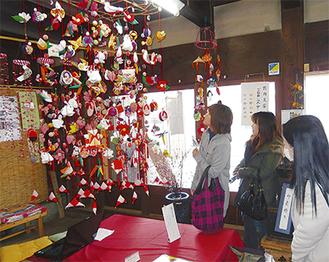 入口に飾られている吊るし雛を楽しむ来館者