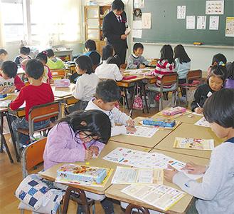 年賀状に絵を描く児童