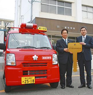 寄贈された車両と中村会長(右)(消防本部提供)