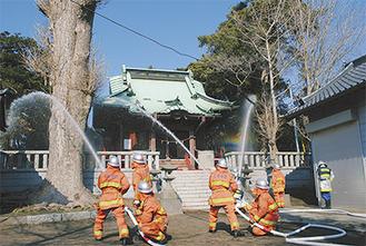 社殿に向け放水する消防署員と団員