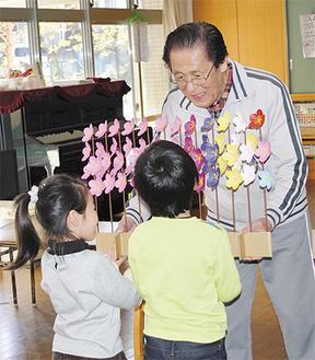 園児に色紙で作った花を手渡す川崎さん