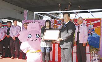 吉田市長から「みうらん」の住民票を受け取るデザインをした落合さん