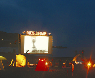 砂浜に設置される300インチの巨大スクリーン(写真は過去/主催者提供)。映画だけでなくレストランやバザー、メリーゴーランドなども登場し、期間限定の夢の空間を演出する