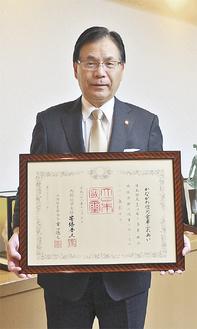 授与された賞状を手にする平松理事長