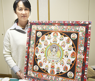 制作中の「仏眼曼荼羅」を手にする長谷川さん