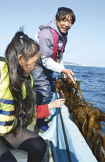 海上で養殖中のワカメを見る児童