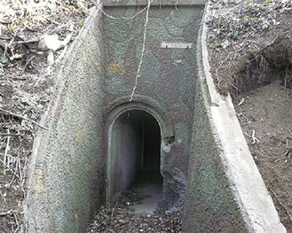 迷彩柄で茂みに隠れる地下壕の入口