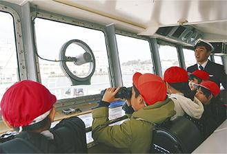 操舵室で双眼鏡をのぞき込む児童たち