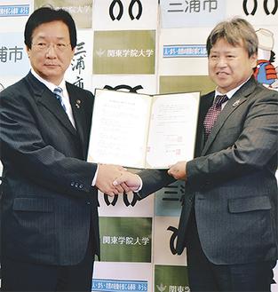 握手をする吉田市長=写真左=と規矩学長
