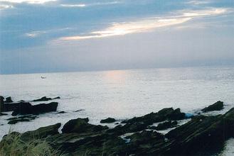 遠く夕日が見える島の浜辺