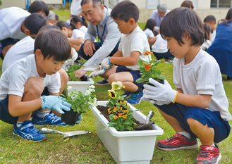 協力してプランターに花を植える児童