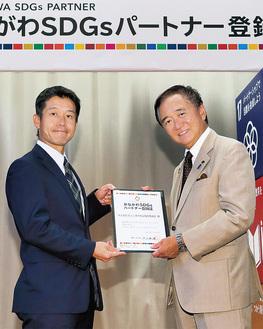 黒岩知事から登録証を受け取る成田事務局長(写真左)