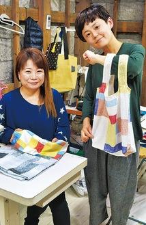 試作のバッグを手にする大類さん(右)と、縫製を担当する木村さん