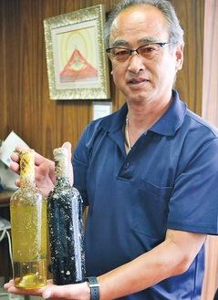 試作の海中熟成ワインを手にする出口浩さん