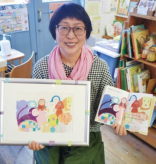 絵本と展示する原画を手にする砂山さん