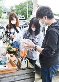 ミキサーでトマトジュースを作る学生たち