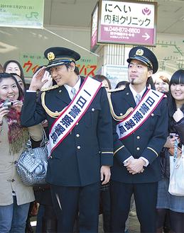 一日署長のタスキをかけて駅前で振り込め詐欺への注意を呼びかける「キマグレン」のKUREIさん(左)とISEKIさん(右)