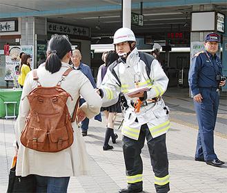 逗子駅前で通行人に設置を呼びかける消防隊員