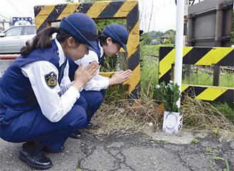 現場の踏み切りで手を合わせる婦人警官