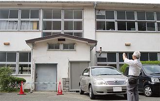 木造校舎の前で写真を撮る鈴木さん