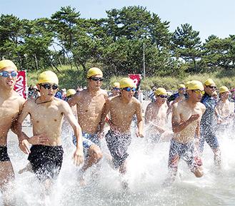 スタートの合図で勢いよく海に向かう参加者