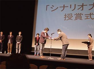 映画監督の瀬々に表彰状を手渡される内田さん