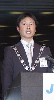 壇上で挨拶する桐田理事長