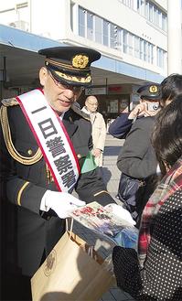通行人にチラシを手渡す福本さん