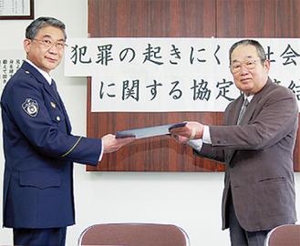 協定書をかわすと向谷署長(右)と柳会長